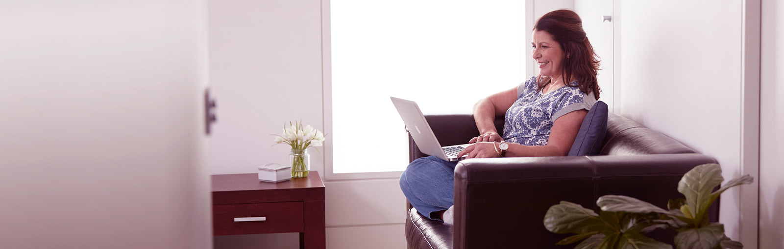 A lady with laptop sitting on brown couch