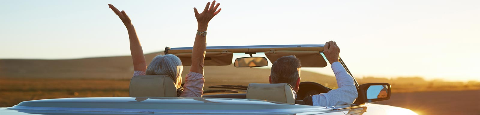 Mature couple in convertible car on open road