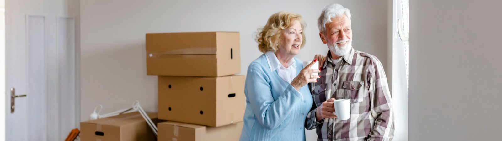 senior woman and man next to moving boxes