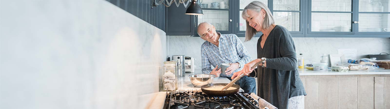 A couple in their 60's cooking & chatting in the kitchen