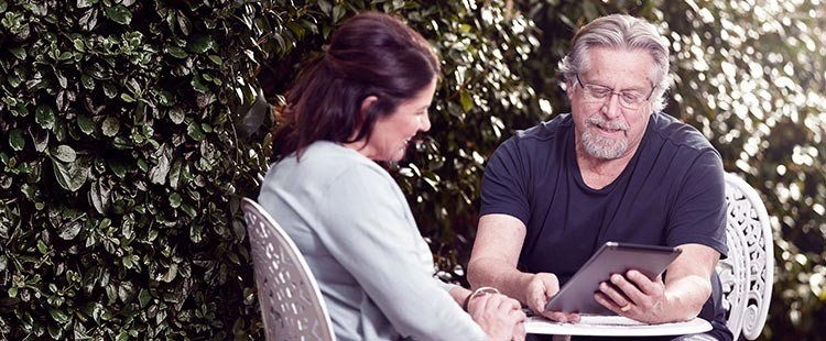 Retired couple on tablet device in garden
